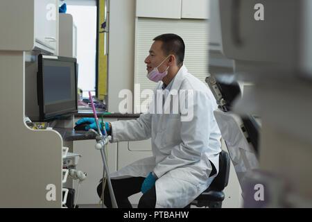 Male dentist utilisant desktop pc en clinique Banque D'Images