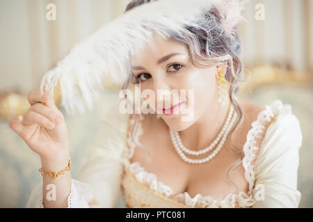 Grayhead femme en robe blanche avec la peau pâle sur fond de style rococo. Une femme vampire avec une belle coiffure avec une plume et stylo dans ses cheveux. bonbon Banque D'Images