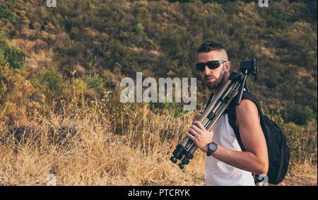 Le jeune photographe avec une barbe, sac à dos sur son dos et le trépied sur son épaule sur la montagne Banque D'Images