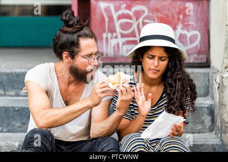 Paris, France - 30 août 2018: Deux jeunes touristes assis manger donuts funny sur trottoir rue dehors en été journée à Florence, Tusca Banque D'Images