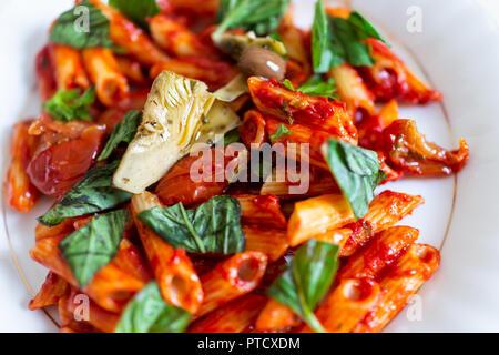 Table à dessus plat, libre d'éclatants de rouge frais sauce tomate pâtes penne sans gluten de maïs sur les nouilles dans la plaque avec le basilic haché marinara verts, articho Banque D'Images