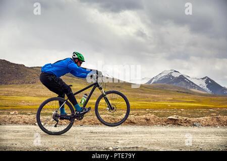 Man on mountain bike rides sur la route dans les hautes montagnes ciel couvert contre l'arrière-plan. Banque D'Images