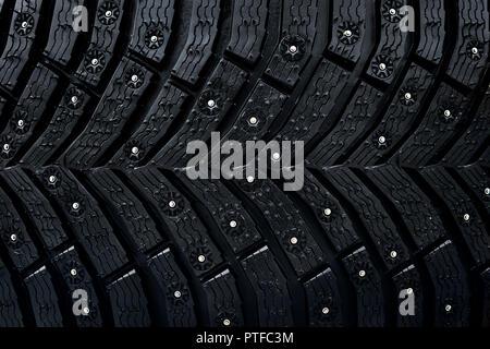 Pneu roue modèle homogène. Un gros plan d'un pneu protecteur et goujons. Pneu d'hiver de texture. Illustration réaliste. En caoutchouc noir, clous et protecteur Banque D'Images