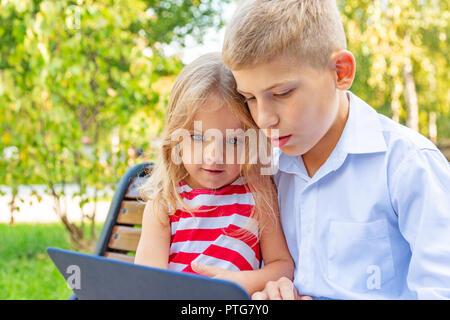 Frère et soeur sourire assis sur un banc dans le parc et jouer sur l'ordinateur portable Banque D'Images