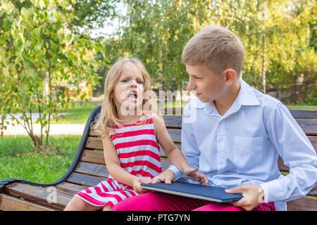 Frère et soeur dans le parc sur un banc à emporter un ordinateur portable de l'autre Banque D'Images