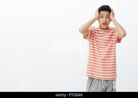 Portrait of young asian guy dans la stupeur en appuyant sur les mains à la tête, bouche ouverte d'étonnement, d'être sans voix, l'expression de l'empathie pour la personne a obtenu dans un accident sur fond gris Banque D'Images