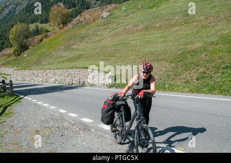 Cycliste fatigué pousse son vélo de la montée raide à Guarda, Suisse autorisation Modèle disponible Banque D'Images
