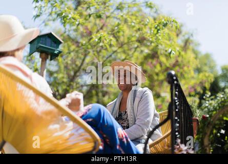 Happy senior women friends talking on sunny patio Banque D'Images