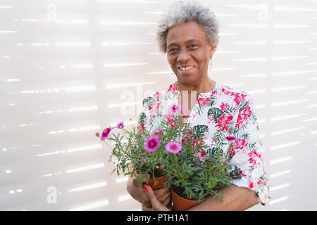 Portrait souriant, confiant active senior woman holding, jardinage pots Banque D'Images