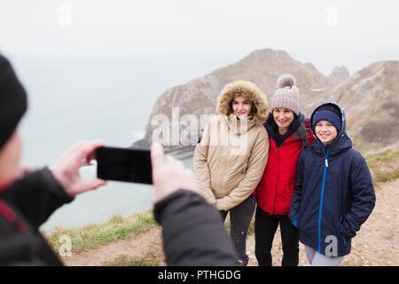 Man with camera phone photographing family dans des vêtements chauds sur la falaise donnant sur l'océan Banque D'Images