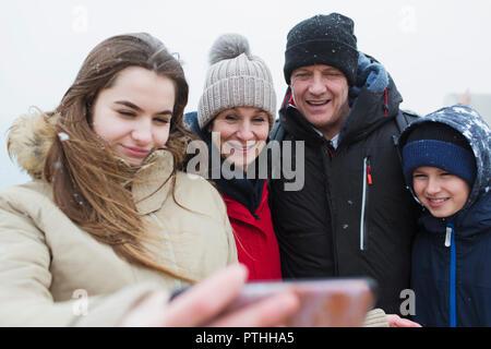 La neige qui tombe sur smiling family prenant selfies Banque D'Images