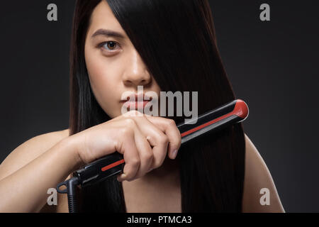 Portrait of young asian woman crêper les cheveux avec Hair Straightener isolated on black Banque D'Images