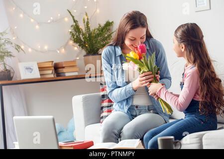 04e780f6041c8 Petit enfant qui sent les tulipes sur la fleur lit dans un beau jour de  printemps  Jeune femme et jeune fille à la maison pour célébrer la fête des  mères ...