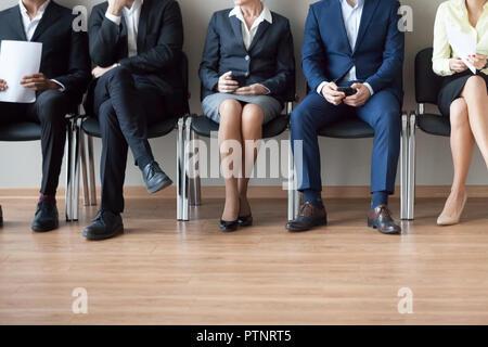 Les jambes de divers travaux d'attente des candidats à leur tour pour l'entrevue Banque D'Images