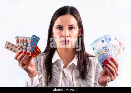 Colorés différents comprimés et gélules en plaquettes thermoformées et billets en euros dans les mains de jeune femme en colère. À directrly dans l'appareil photo. Isolé sur un Banque D'Images