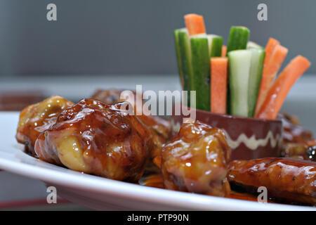 Close-up d'ailes de poulet à la sauce barbecue avec des bâtonnets de légumes courgette et carotte - la cuisine mexicaine Banque D'Images