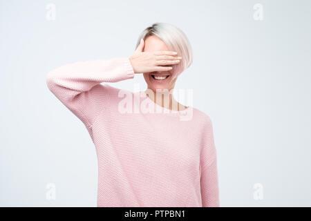 Happy young woman standing sur fond gris et couvrant les yeux. Elle est en attente de proposition ou de don Banque D'Images