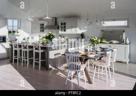 Cuisine ouverte et salle à manger avec vue sur la mer à l'unité de l'île de tabourets de bar avec table à manger et chaises en côte ensoleillée home Banque D'Images