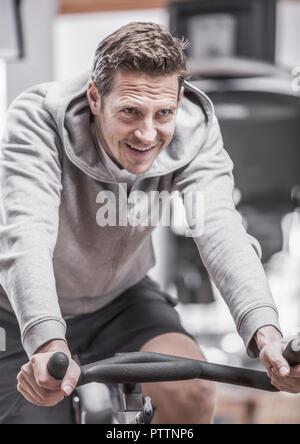 Mann im Fitness-Studio, trainiert auf Radergometer (modèle récent) Banque D'Images
