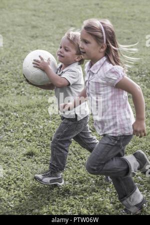 Kleiner Junge und Maedchen mit - Fussball ueber Wiese (modèle récent) Banque D'Images