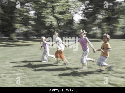 Vier Kinder) de pair ueber Wiese, Bewegung (modèle récent) Banque D'Images