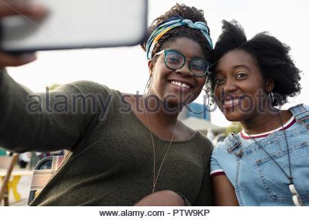 Portrait smiling sisters en tenant avec selfies téléphone appareil photo Banque D'Images