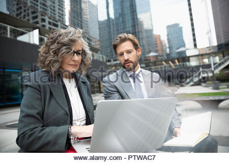 Businessman and businesswoman working at laptop in city plaza Banque D'Images