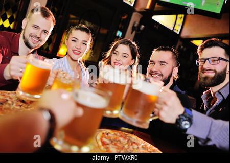 Happy woman boire de la bière pression et verres clink dans un bar ou pub Banque D'Images