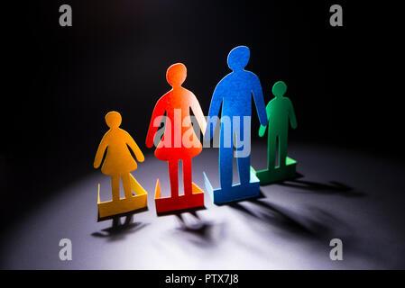 La famille de papier de couleur sur un fond sombre. Banque D'Images