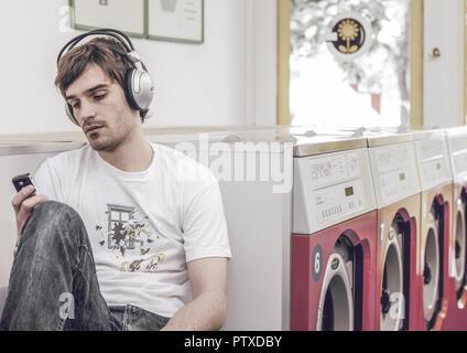 Mann sitzt im Waschsalon, hoert Musik (modèle récent)