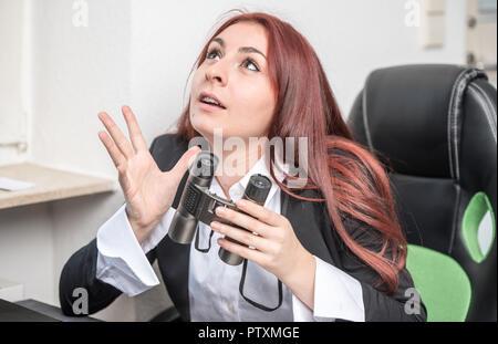 Jeune femme d'affaires dans le bureau, assis à un bureau devant un ordinateur portable, holding binoculars dans ses mains, elle dit quelque chose, explique Banque D'Images