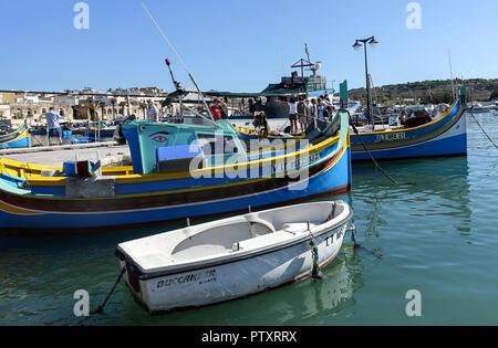 Peints aux couleurs vives, des bateaux de pêche maltais traditionnel dans le port de Marsaxlokk, Malte Banque D'Images