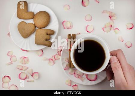 Lettre d'amour à partir d'un cookie, main tenant une tasse de café sur un fond blanc Banque D'Images