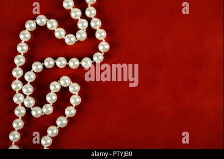 Collier de perles blanches sur fond de cuir brun rougeâtre.