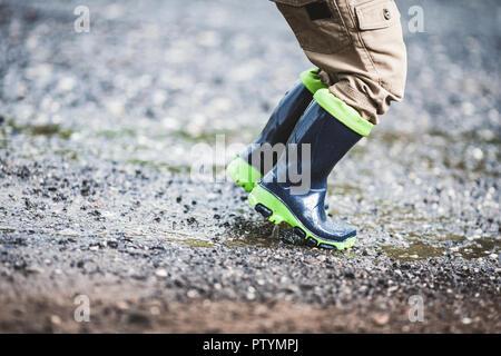 Close up sur l'enfant en portant des bottes en caoutchouc par temps de pluie