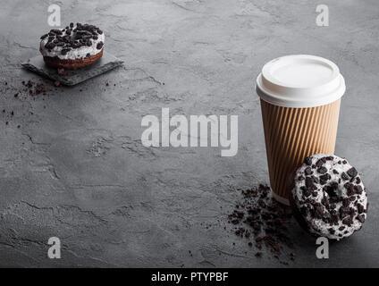 Tasse à café en carton noire avec cookies donuts sur fond noir table de cuisine en pierre. Boire un Café et collation. Banque D'Images