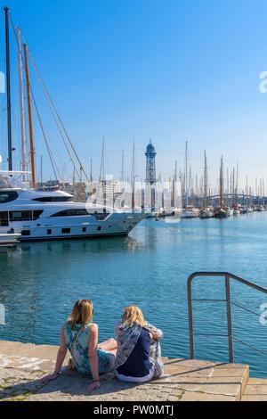 Deux jeunes femmes assises sur le quai dans le Port Vell (vieux port), Moll de Bosch i Alsina, Barcelone, Espagne Banque D'Images
