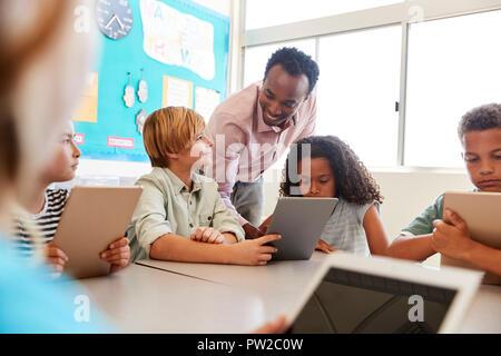 Enseignant parmi les enfants avec des ordinateurs dans la classe de l'école élémentaire Banque D'Images