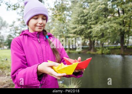 Fille en bleu et chapeau veste magenta tenant deux bateaux en papier de couleur piscine près de la rivière sur jour d'automne Banque D'Images