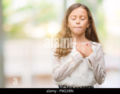 Brunette woman smiling avec les mains sur la poitrine avec les yeux fermés et reconnaissant geste sur la face. Concept de santé. Banque D'Images