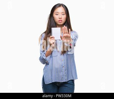 Young Asian woman holding notebook sur fond isolé avec main ouverte faisant stop avec de sérieux et de confiance, l'expression gestuelle de la défense