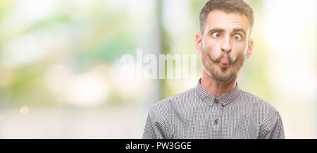 Jeune homme hipster fait face avec les lèvres, fou et geste comique. Drôle d'expression. Banque D'Images