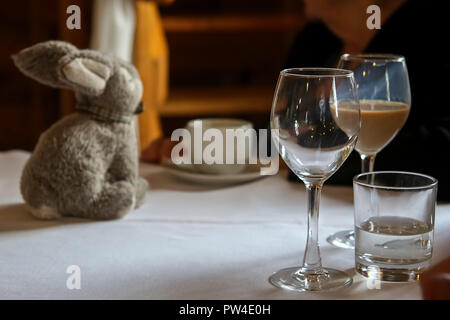 Verre à liqueur de crème irlandaise, verre vide, verre d'eau, tasse de café et le lapin sur la table. Banque D'Images