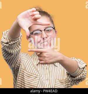Jeune blonde business woman smiling décisions cadre avec les mains et les doigts avec un visage heureux. La créativité et la photographie concept. Banque D'Images