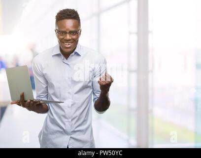 Young african american businessman using computer laptop crier fier et célébrer la victoire et le succès très excité, encourageant l'émotion Banque D'Images