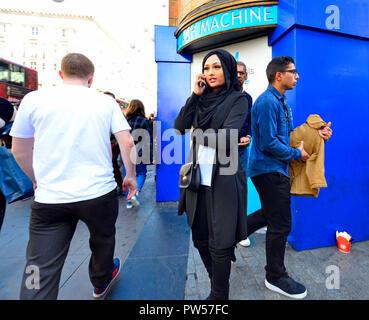 Femme Asiatique portant un foulard en utilisant son téléphone portable, Londres, Angleterre, Royaume-Uni.