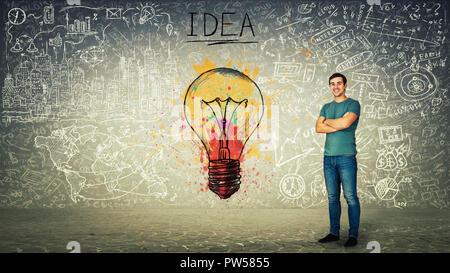 Heureux confiant young man smiling, mains croisées, ampoule colorée et des croquis sur l'arrière-plan. Unicité de l'idée et concept genius.