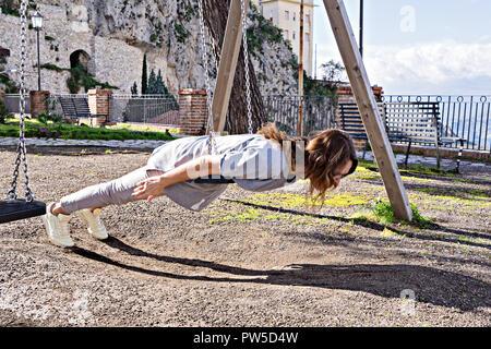 Joyeux, Merveilleux hipster girl à décontractée et cheveux au vent, de jouer sur les planches de swing, deadpan style photo, effet instagram Banque D'Images