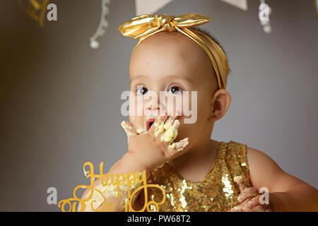 Petite fille Bébé doux dans une robe d'or avec un arc sur la tête d'essayer un gâteau de gelée jazzy une crème. studio shot of un anniversaire sur fond gris entouré par des boules Banque D'Images