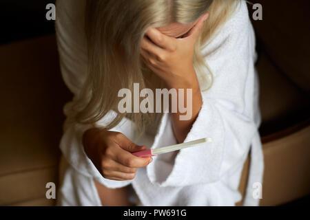 Dans la salle de bain femme concernée à l'aide de test de grossesse à domicile Banque D'Images